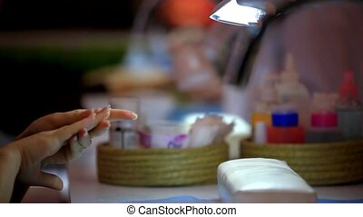 Client prepares to hand for manicure in beauty salon. Womans...