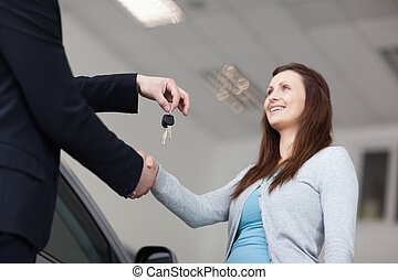 Client receiving car keys while shaking hand