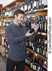 client, regarder, bouteille vin, dans, magasin