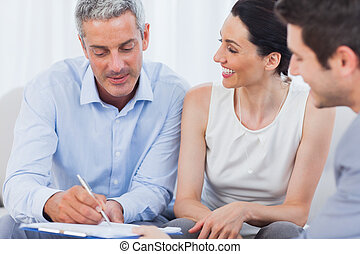 Client signing a contract with wife held by salesman on...