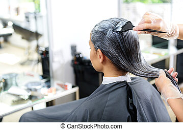 client sitting in a chair at the beauty salon