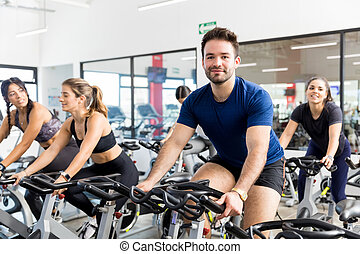 Client Smiling While Exercising On Bike With Friends In Gym