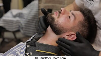 Client with black beard during beard shaving in barber shop....