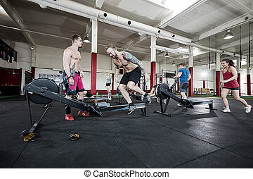 Clients Exercising In Fitness Club