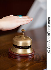 Client's Hand Over Bell At Hotel Reception