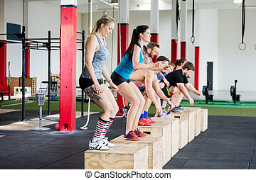 Clients Practicing Box Jumps In Row At Fitness Studio - Male...