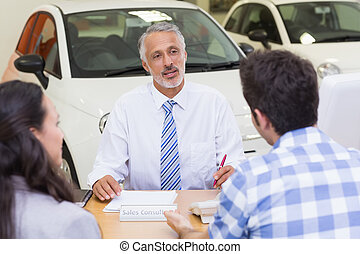 Clients talking with a dealer at new car showroom