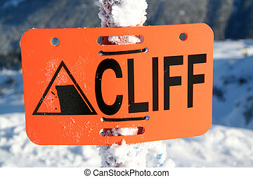 A sign at a ski hill warning skiers of a cliff ahead.