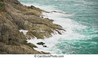 Cliff in the tropical ocean, close up. Turquoise sea water splashes against the shore