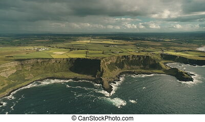 Cliff ocean Ireland shore aerial view: green grassy valley with little farms in countryside. Majestic rural Irish at deep blue water under grey cloudy sky. Autumn cinematic drone shot in 4K, UHD