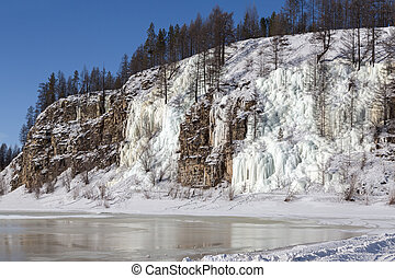 Frozen water streams on a rocky cliff in South Yakutia, Russia