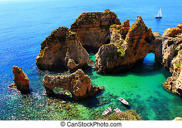Cliffs at the Algarve coast in Portugal with boats