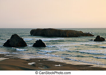 Cliffs on the coast of the Pacific Ocean during sunset in summer