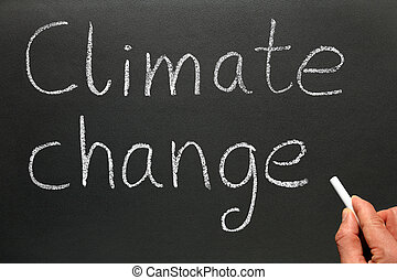 Climate change. - A teacher writing Climate change on a...