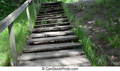 climb walk upstair wooden stairs with railing and old stone pagan altar on top of hill.