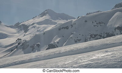 Climb up on cable car. Snowy mountains, ski run. Sunny day. North Caucasus.