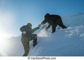 Climber assists another climber on the slope of snowy mountains