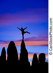 Climber balances on the summit. - Climber is silhuetted on ...