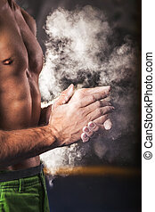 Climber man coating his hands in powder chalk magnesium