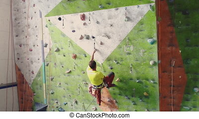 Climber moves on the mountain in a room with a rope on the...