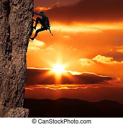 girl climbing on the rock on sunset background