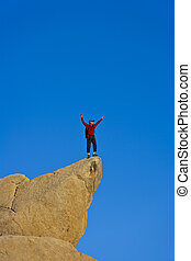 Climber on the summit of a rock spire after a successful ascent, in the Sierra Nevada Mountains, California.