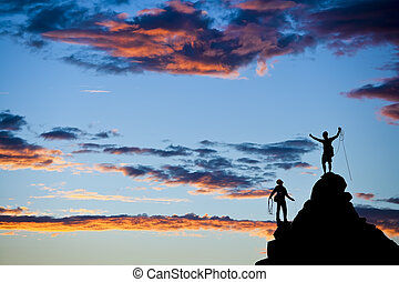 Team of climbers silhouetted as they coil ropes after reaching the summit of a rock pinnacle in The Sierra Nevada Mountains, California.