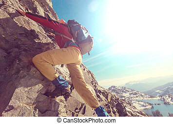 Climber scrambling up by rocky terrain