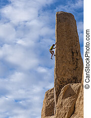Rock climber clings to the edge of a challenging cliff in Joshua Tree National Park.