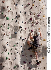 Climber Traversing Rock Wall - A climber on a rock wall with...