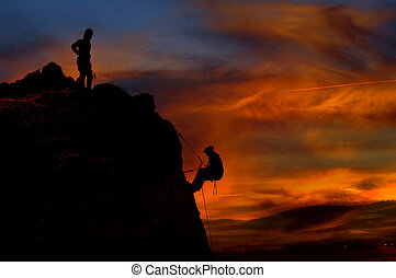 Climber waiting his partner on the summit. Beautiful sunset in the background