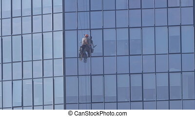 climber washes windows in a skyscraper with blue sky
