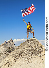 Climber waves flag on mountain peak.