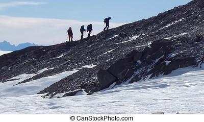 Climbers climb the mountain with snow field. Four climbers...