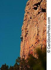 Climber scaling rock wall at Sand Gulch.