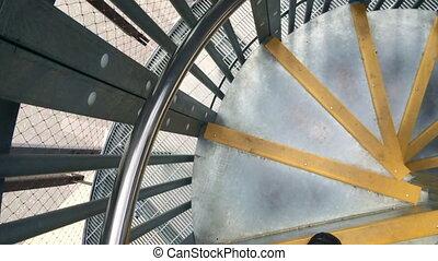 Climbing down spiral staircase - Person climbing down...