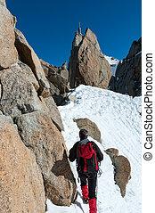 Climbing in Chamonix. Climber on the snowy ridge of Aiguille du