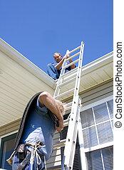 Climbing ladder - Roofer repairing damaged shingles after...