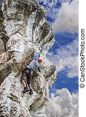 Climbing man with high stone rock and blue sky