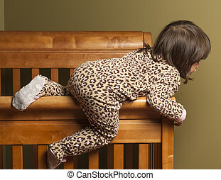 Climbing out of the crib - Toddler climbing out of her crib.