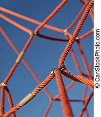 Climbing rope net with blue sky background. Close-up of part of a sports and gaming complex.