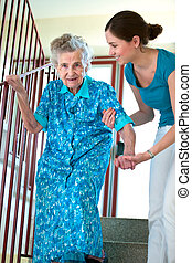 Climbing stairs with caregiver - Senior woman is climbing ...
