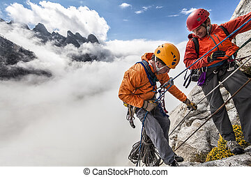 Team of climbers rappelling the cliff during a storm.