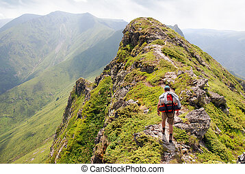 Climbing the mountain - Climber walking at the edge of steep...