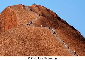 People climbing the famous Uluru or Ayers Rock in Central Australia