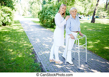 Pretty carer walking out with senior patient