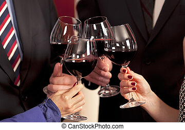 Clinking glasses and toasting with red wine in celebration.