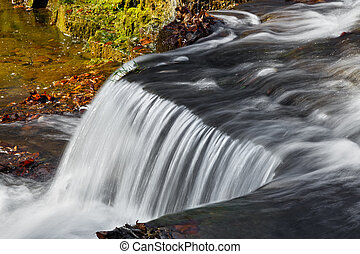 Water flows over a jagged rock ledge of Clinton Falls, a waterfall in rural Putnam County, Indiana.