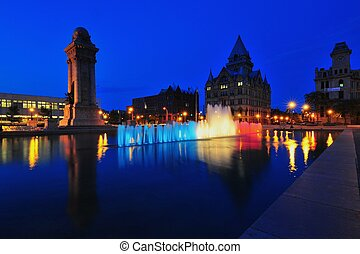 Buildings and monuments at Clinton Square reflected in the fountain pool in Syracuse, New York.