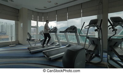 Clip of woman on the treadmill in fitness centre looking at window with cityscape. Hong Kong, China